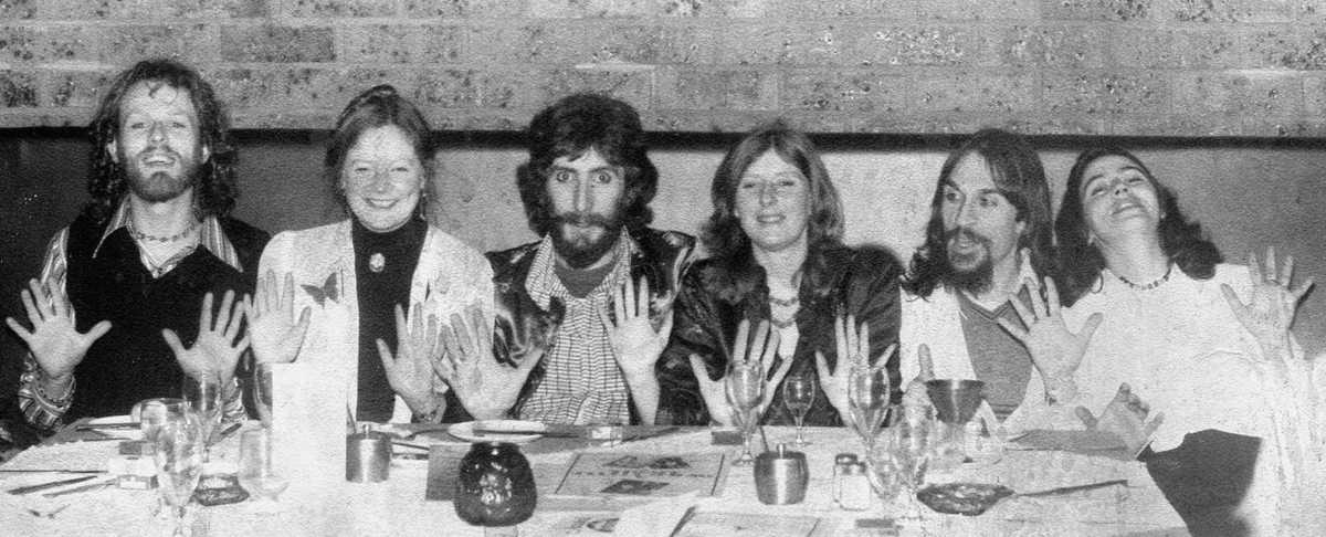 6 original Handspan members at dinner table with their hands held open in the company logo